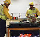 Photo showing LES line techs doing a high-voltage tabletop demo